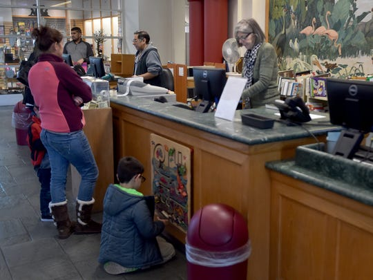 Visitors line up at the check-out counter at the Oxnard Library on a recent Tuesday.
