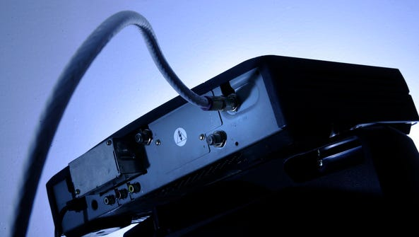 A cable box is mounted on top of a television.