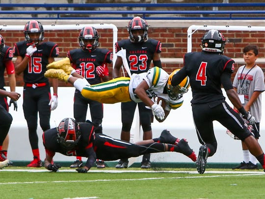 Harrison senior Devon Pressley goes airborne after being submarined by an East Kentwood tackler.