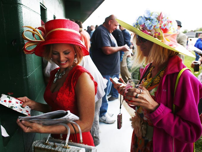 Karen Doyle, right, and Mary Zoeller make early bets at the wagering window in the infield at The Kentucky Oaks.   May 2, 2014