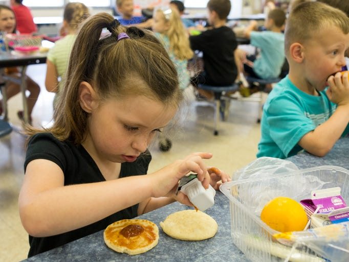 From left, Jenna Chilton, 6, Mason Mills, 5, and Kayla Nelson, 10, eat lunch at Bates Elementary School. All students at 95 schools across Jefferson County Public Schools will be allowed to eat both breakfast and lunch for free starting this fall, under an agreement between the district and the U.S. Department of Agriculture and the National School Lunch Act. June 9, 2014.