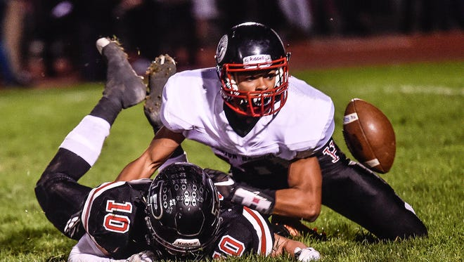 Marion Harding's Dejaun Smith and Pleasant's Josh Warner dive for a fumbled football during the Marion Harding vs Pleasant football game on Friday night.