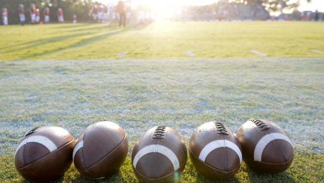 Footballs line the field before a game.