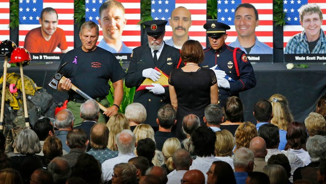 An honor guard presents  families with an American flag during a memorial service in Prescott Valley, Ariz., on July 9, 2013, for 19 firefighters who were killed battling the Yarnell Hill Fire outside.