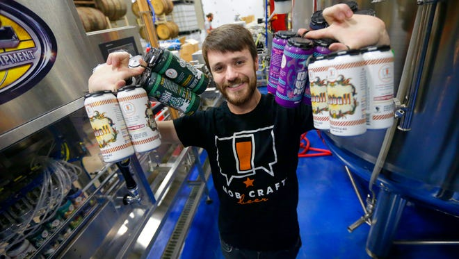 Henry Schwartz, founder and CEO of MobCraft brewery, holds an assortment of beers Monday in the canning area at MobCraft, 505 S. 5th St. Brewers are worried about a proposed tariff on aluminum from overseas, which would raise the cost of canning beer.