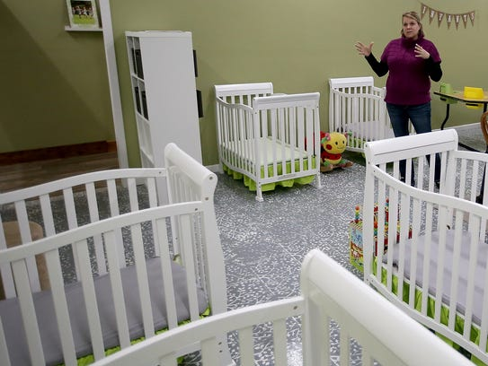 Katie Hudkins stands among the cribs in the infant