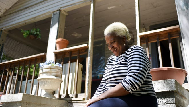 Loretta Bowman sits outside of her house after flood waters entered her home last month. Volunteers of the Carpenter's Helper program are in the process of fixing the damaged rooms.