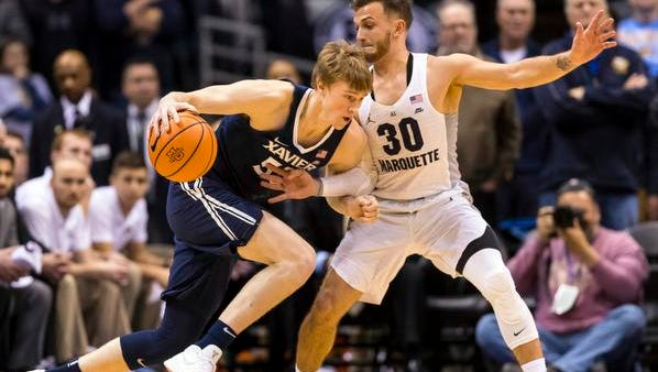 Xavier guard J.P. Macura (55) drives for the basket as Marquette Golden Eagles guard Andrew Rowsey (30) defends during the first half at BMO Harris Bradley Center.