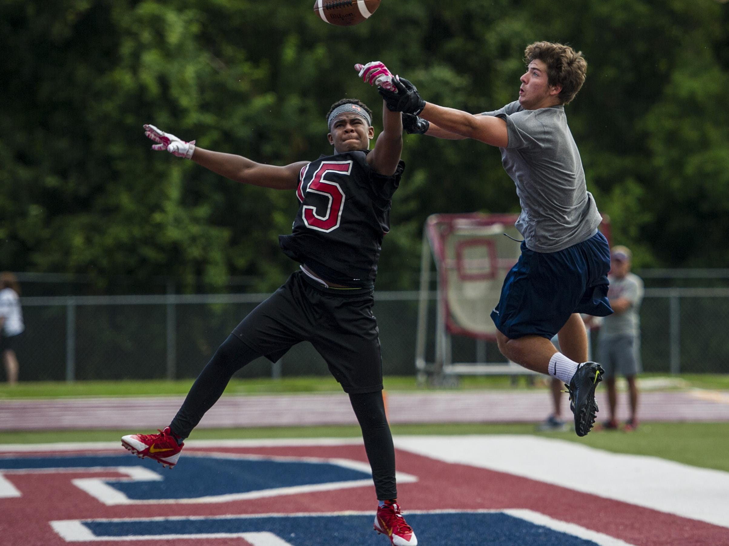 Northside's Theo Rose swipes the football away from Teurlings' Jansen Lormand during a game in the 7-on-7 Showcase hosted by Quick Slants Magazine at St. Thomas More Catholic High School in Lafayette, La., Thursday, July 16, 2015.