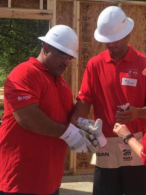Toa Mariota and his son Marcus Mariota, quarterback of the Tennessee Titans, helped build a Habitat for Humanity home in Nashville Friday along with four other Heisman Trophy winners.
