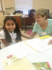 Mary Lynn Moser, right, a New Horizons volunteer, tutors Leslie, a young Super Kids Club member.