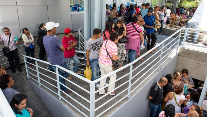 People line up outside a pharmacy on Jan. 20, 2015, in Caracas, Venezuela.