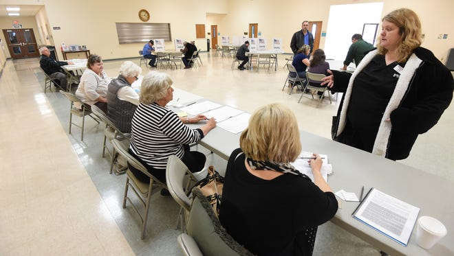 Mountain Home resident Vicki DeSerisy, satnding far right, talks Tuesday with poll worker Janie Edmonds-Lewis, seated far right, as the pair try to determine DeSerisy's voter status at East Side Baptist Church.