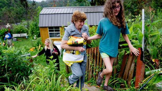Ashley Crouch leads Glenna Ogle to her new home during the house dedication ceremony for Glenna Ogle, who lost her home during the November 28 wildfires in Gatlinburg, Tennessee on Friday, July 28, 2017. The home is the first of 25 homes to be built for fire victims by Appalachia Service Project.