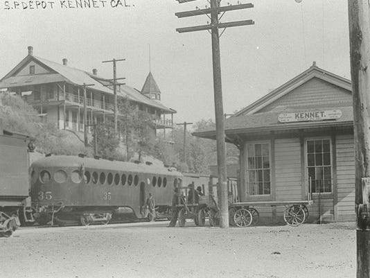 This 1909 image shows the Southern Pacific Railroad Depot at Kennett on Railroad Avenue. A train is parked at the depot. The Trinity Land & Copper Company building appears on the hill side to the left.  Note: the spelling of the name of the town on the depot sign. Courtesy of Shasta Historical Society.