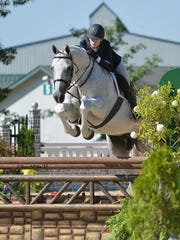 Carter Anderson and Charleston go for a jump during an equestrian event.