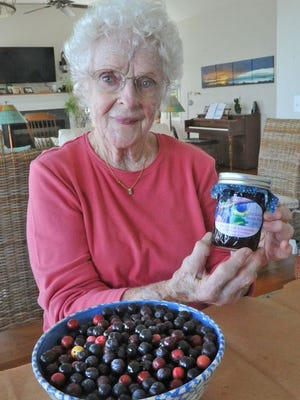 Lois Murphy with one of her jars of beach plum jam in her Houghs Neck kitchen.
