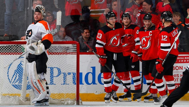 NEWARK, NJ - FEBRUARY 01:  Nico Hischier #13 of the New Jersey Devils celebrates his goal late in the third period against Alex Lyon #49 of the Philadelphia Flyers with his teammates on February 1, 2018 at Prudential Center in Newark, New Jersey.  (Photo by Jim McIsaac/Getty Images)