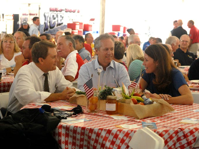 Commissioner of Agriculture James Comer, left, Louisville Mayor Greg Fischer, center, and Secretary of State of Kentucky Alison Lundergan Grimes, right, prepare to listen to speakers during the commodities breakfast that opens Kentucky State Fair.  Aug. 14, 2014