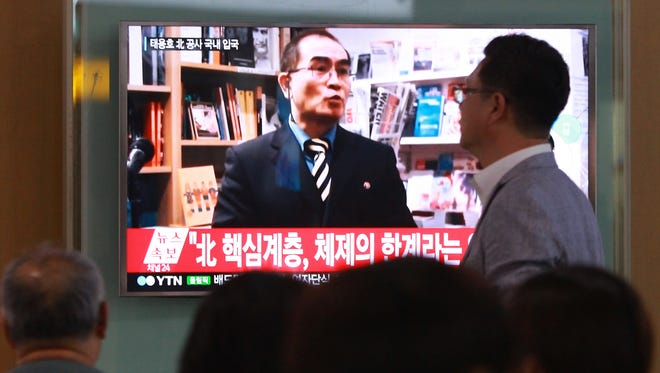 People watch a TV news program showing a file image of Thae Yong Ho, minister at the North Korean Embassy in London, at Seoul Railway Station in South Korea on Aug. 17, 2016.