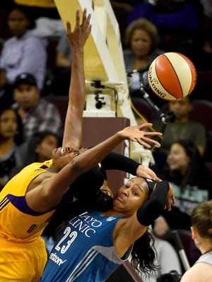 Los Angeles Sparks forward Nneka Ogwumike (30) and Minnesota Lynx forward Maya Moore (23) reach for a rebound in the second half Friday at Galen Center in Los Angeles.