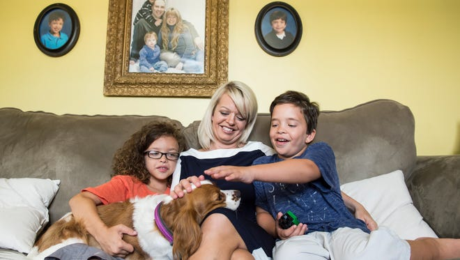 Anna Corbin sits between her two sons, Jackson (left) and Henry (right), as they play with their dog, Eloise, inside their Hanover home. Henry, 9, and Jackson, 11, both have Noonan syndrome - a genetic disorder that affects various systems of the body -- and both boys have been active in lobbying against potential cuts to Medicaid.