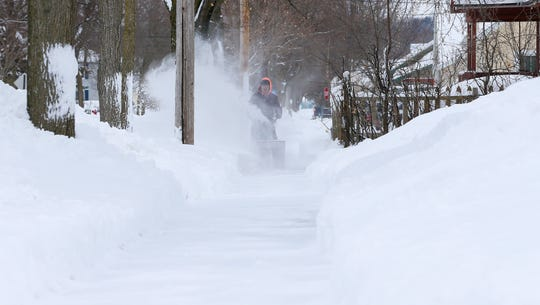 A resident clears his sidewalk along Bopf Street Monday,