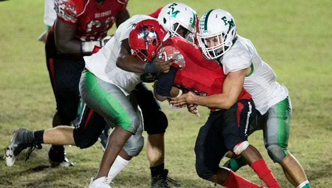 Fort Myers High School defenders tackle North Fort Myers' Terry Lindsey for a loss on Friday in the regional semifinal game at North Fort Myers. Fort Myers beat North 7-6 and will play Naples in the upcoming regional final.