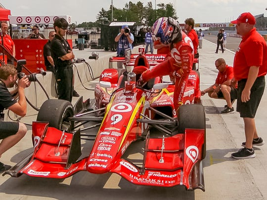 Scott Dixon climbs into the car on pit road at Watkins Glen International at the start of the IndyCar test session at the track.