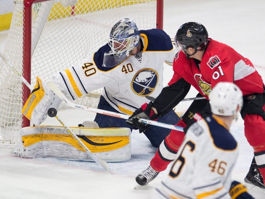Buffalo Sabres' goalie Robin Lehner knocks away a shot from Ottawa Senators' right wing Mark Stone (61) as Sabres' Cody Franson looks on during the first period of an NHL hockey game, Tuesday, Feb. 16, 2016 in Ottawa, Ontario.  (Adrian Wyld/The Canadian Press via AP) MANDATORY CREDIT