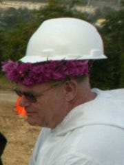 Father Jack Niland, wears a hard hat during the 2006