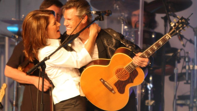 Presidential candidate Michele Bachmann hugs country singer Randy Travis in her tent at the Republican Party's straw poll in Ames in 2011. Bachmann won the straw poll while eventual GOP nominee Mitt Romney ignored it. Critics of the straw poll dislike its pay-to-vote process.