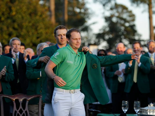 Defending champion Jordan Spieth, left, helps 2016 Masters champion Danny Willett, of England, put on his green jacket following the final round of the Masters golf tournament Sunday, April 10, 2016, in Augusta, Ga. (AP Photo/Chris Carlson)