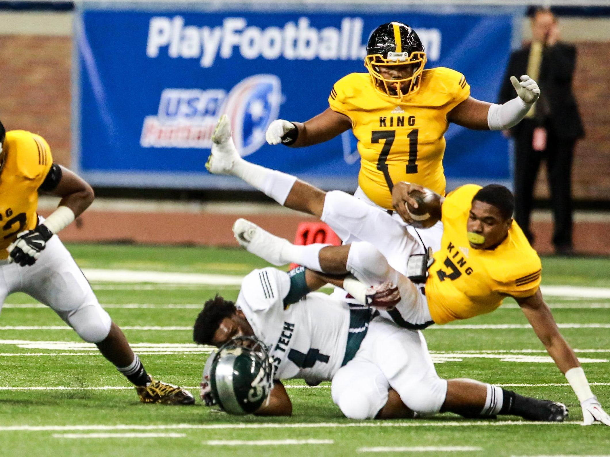 Detroit King QB Armani Posey is tackled by Detroit Cass Tech's Taron Young, who loses his helmet in the process, in the Division I title game.