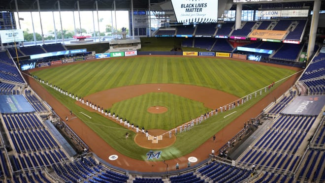 Miami Marlins players, left, and Atlanta Braves players, right, stand to honor Black Lives Matter before the start of a baseball game, Friday, Aug. 14, 2020, in Miami.