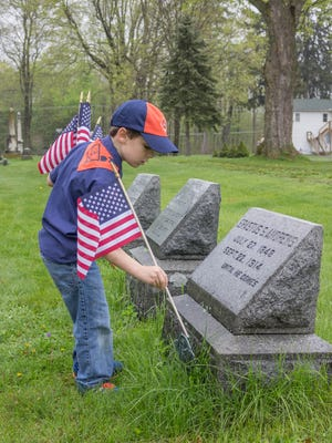 Tiger Cub Scout Basil Metz places a flag on a veteran's grave.