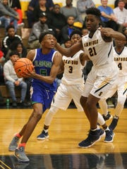 St. Georges' Nah'Shon Hyland goes to the basket against Sanford's Nnanna Njoku in Sanford's 61-40 home win Tuesday.