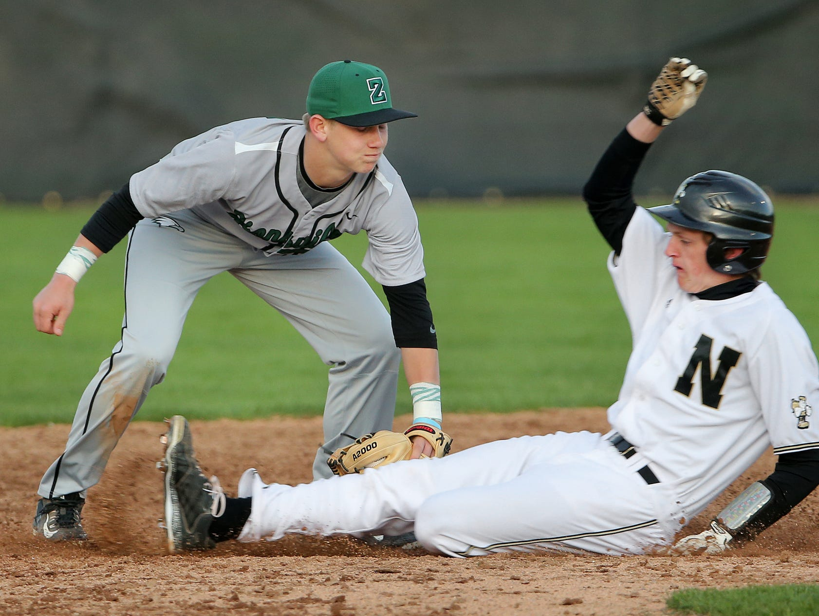 Zionsville's Riley Bertram tags out Noblesville's Jackson Thurman at second base, April 22, 2015.