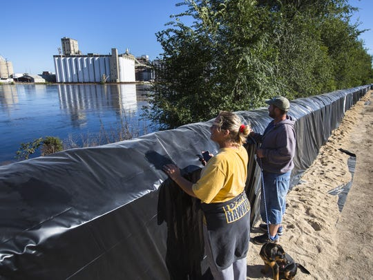 Ronnee Peterson and her son, Stanley McGraw, check the water level at the Cedar River rises a few blocks from Peterson's Cedar Rapids home Monday, Sept. 26, 2016.