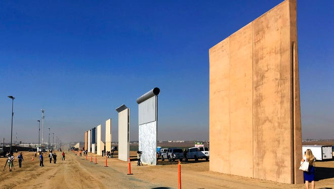 This Oct. 26, 2017 file photo shows prototypes of border walls in San Diego. A U.S. official says recent testing of prototypes of President Donald Trump's proposed wall with Mexico found their heights should stop border crossers.