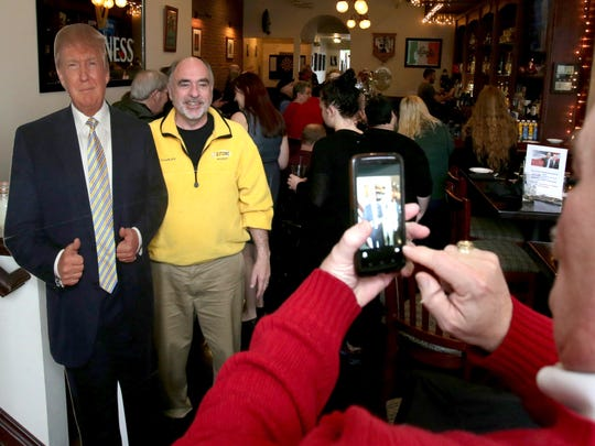 Rod Charles of Oxford has his picture taken with a Donald Trump cutout by Bill Holt of Lake Orion. They are members of GOGOP, the Greater Oakland Republican Club, who hosted a watch party inside the Sullivan's Public House in Oxford on Friday, January 20, 2017.
