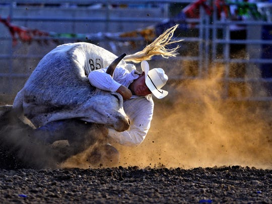 Shawn Downing competes in the steer wrestling event