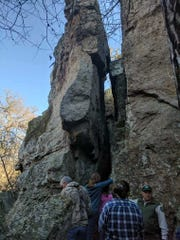 "Park Ranger David Owens directs tour participants into ""The Squeeze"" rock formation at Penitentiary Hollow at Mineral Wells State Park and Trailways."