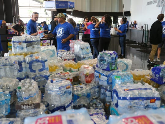 Volunteers hand out donations to residents affected