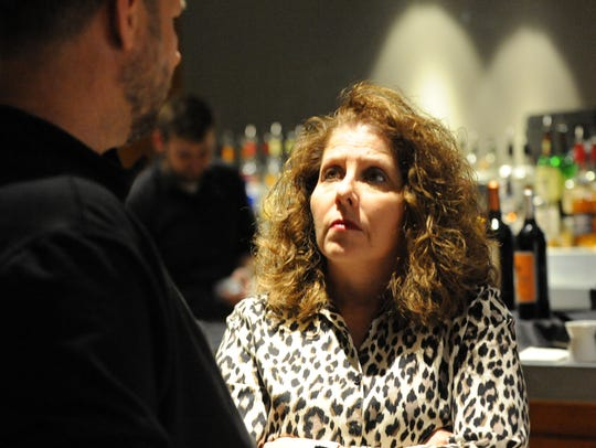 Holly Miller-Downour talks to people Tuesday night,