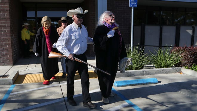 The Lone Stranger and Sidekick are escorted out of Cornerstone Community Bank in Redding on Monday morning after the Asphalt Cowboys bank robbery launched Redding Rodeo Week activities.