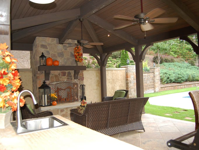 This undated photo provided courtesy of Blackmon Rogers Architects LLC, of Birmingham, Ala, shows the stone fireplace with Masonry fireplace insert by Isokern in the sitting area which extends the season into cool fall evenings in the Smith hangout house by the pool in Trussville, Ala. Two years ago, Tammy Smith and her husband, added a $115,000 open-air pool house, decked out with fireplace, large TV, refrigerator, two grills and couches, to make the pool area attractive year round. Their daughters hung out there with friends, watching TV and making s?mores.