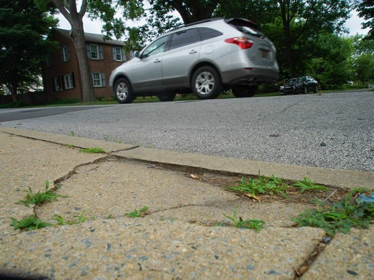 A vehicle passes by a broken sidewalks along W. 9th