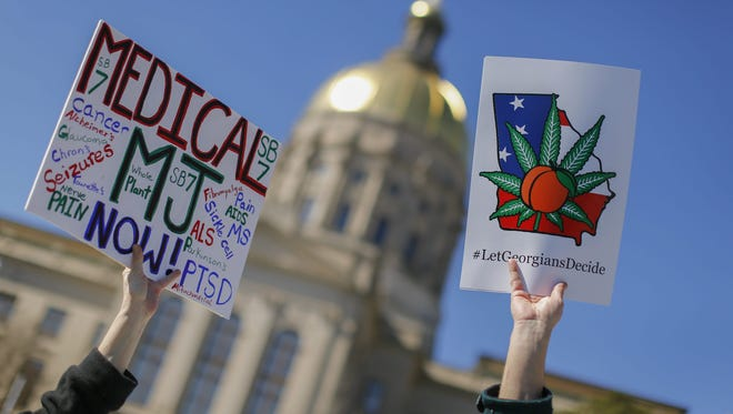 People hold signs while participating in the pro-marijuana Rally for Peace, Justice and Unity outside the Georgia State Capitol in Atlanta on Feb. 10, 2015.