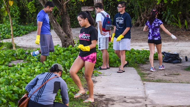 Paluma Junior Achievement company members and other supporters participate in a coastal cleanup in and along the shoreline of Matapang Beach in Tumon during the morning of Saturday, Dec. 23, 2017.